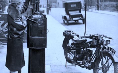 A lady fills a vintage motorcycle in a very old picture