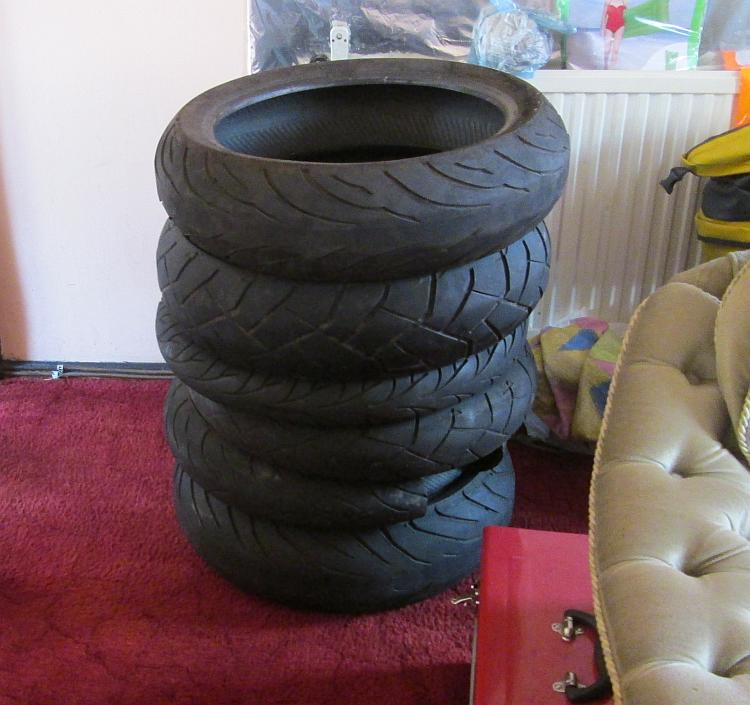 A stack of used motorcycle tyres in Ren's living room