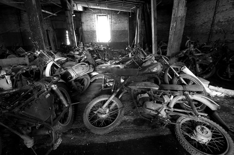 scrappy old motorcycles in a dirty shed