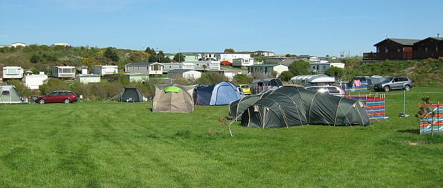 tents on a gren field with static campervans on the hillside