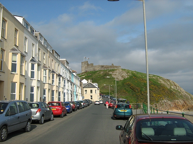 criccieth castle ontop of the hill, seen from a road lined with guesthouses