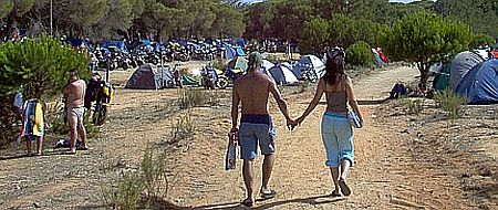 2 people surrounded by tents and bikes hold hands and walk in the glorious sunshine