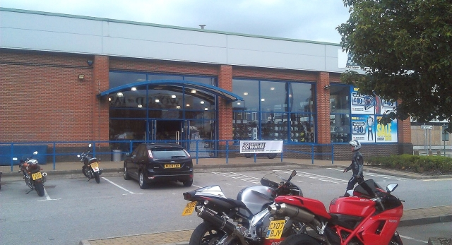 a large shop with a few bikes in the car park, george white's bolton