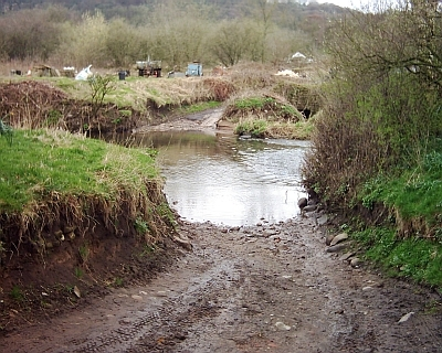 a muddy track leading to a deep river