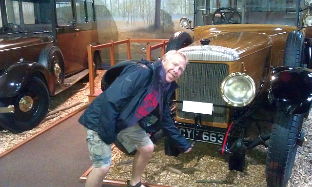 iw holding the cranking handle of an old car at the museum