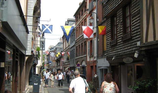 a narrow and old street with overhanging buildings and bunting, busy and bustling with shoppers