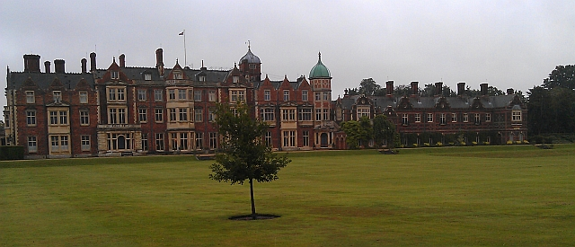 Sandringham house, a long 3 storey brick built house with chimneys, many windows and manicured lawns