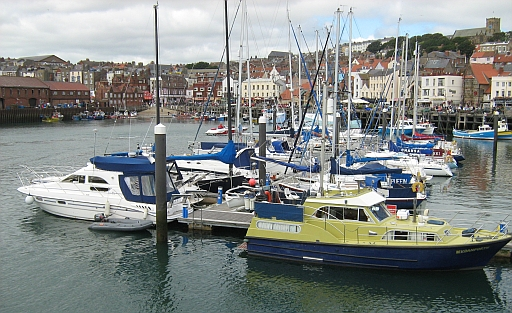 scarborough harbour with boats, the surrounding shops and hotels and on the hill st mary's church