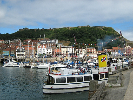 Scarborough Harbour with boats and small ships and the castle walls in the background