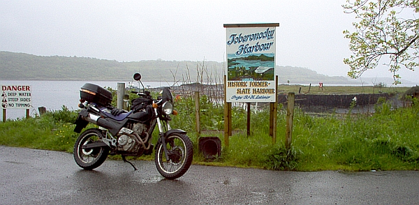 my bike next to a sign saying toberonochy harbour in the rain