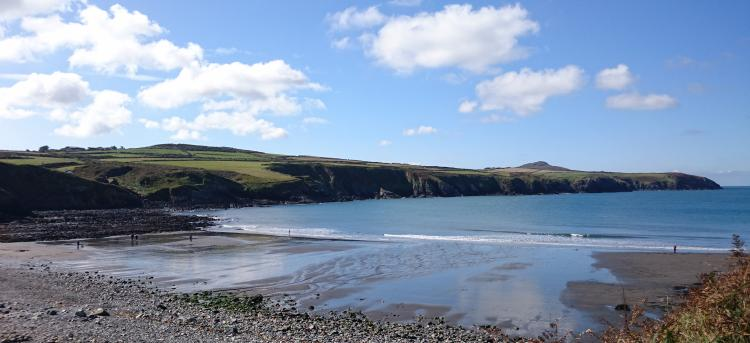 Abereiddy Beach, stones and pebble lead to sand and the sea between outcrops