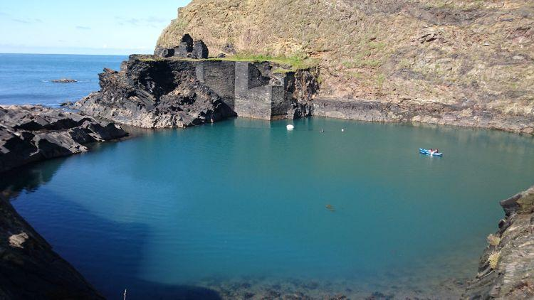 Steep slate mine walls lead into a deep turquoise pool at The Blue Lagoon