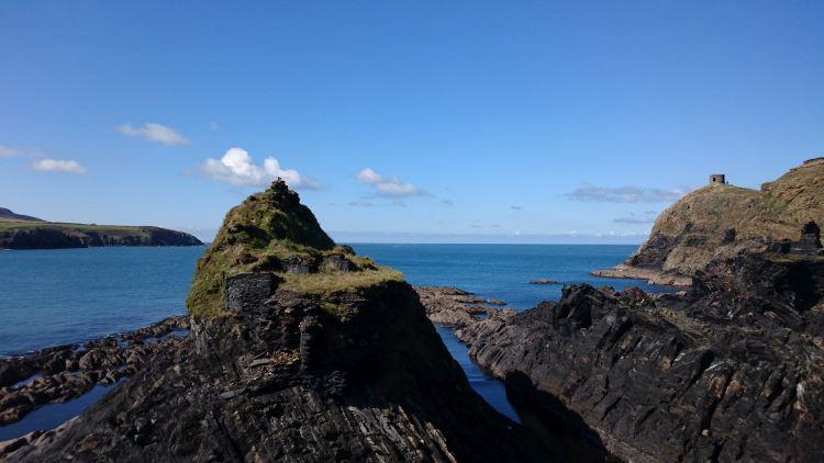 Jagged angular outcrops of slate rock set against a blue sky with the sea and coast behind