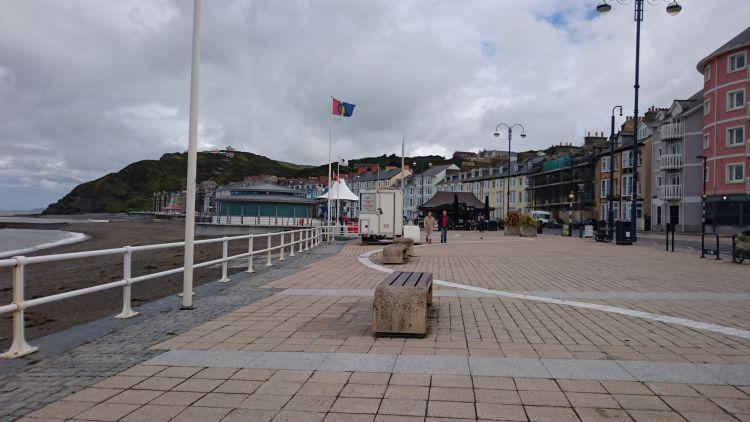 The sweeping curve of Aberystwyth promenade, a beach, hills and a broad footpath