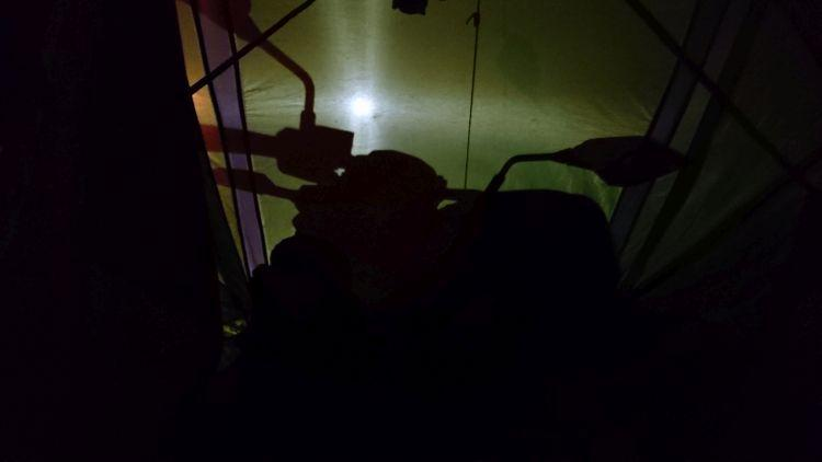 A bright eerie light outlines a motorcycle against the material of the tent.