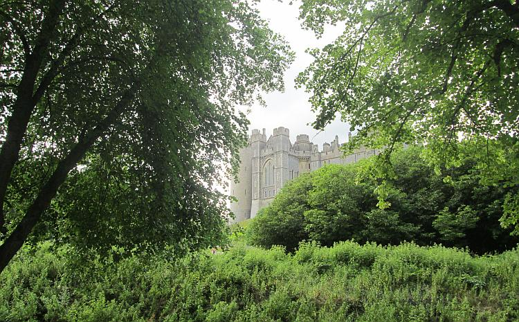 The towering walls of Arundel Castle seen between trees and shurbs