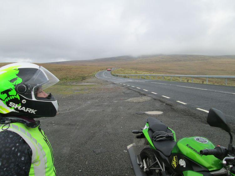 Sharon looks out across misty moors and a lonely road on The Black Mountain Pass