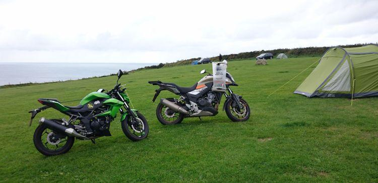 The 2 motorcycles and the tent set against the sloping field and the hazy sea at Caerfai Bay