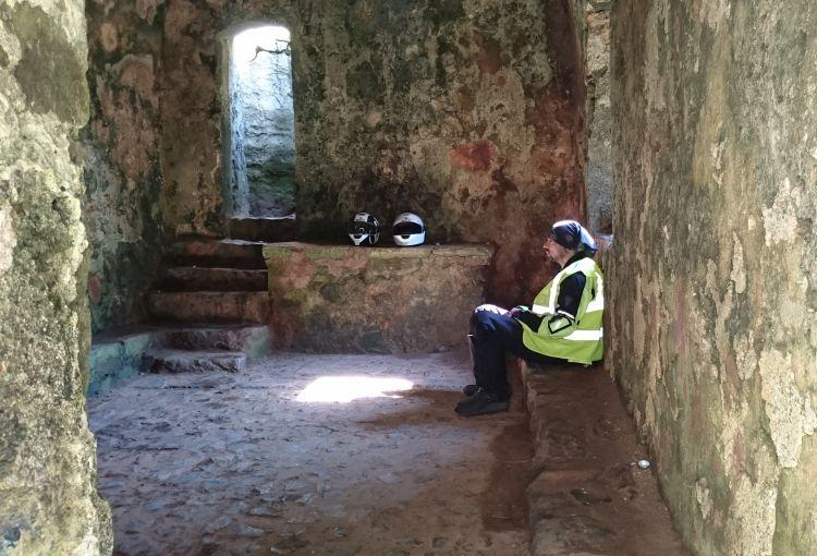 Ren sits on the hard stones of St Govan's Chapel