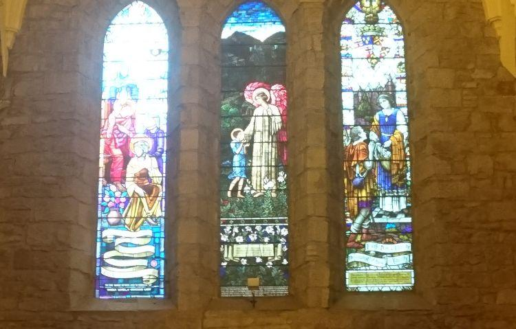 3 narrow arched windows filled with stained glass images at Dornoch Cathedral