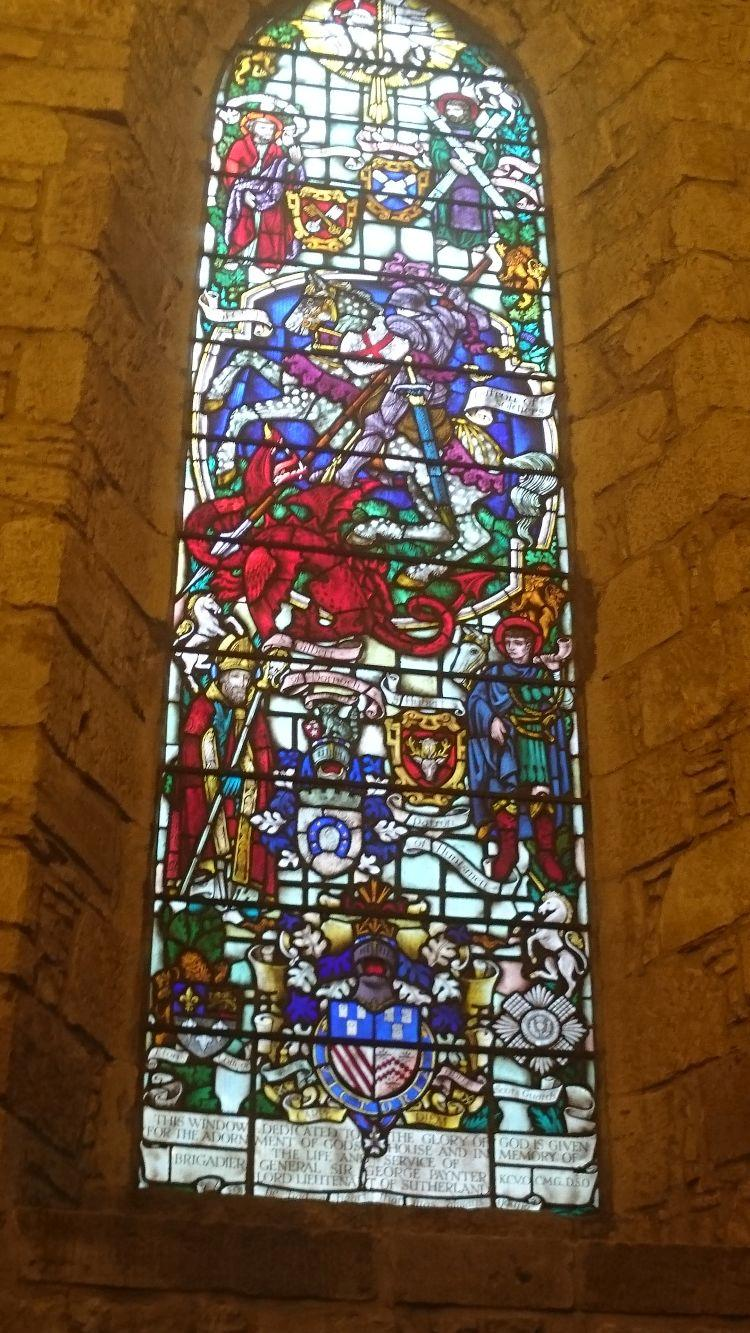 A tall stained glass window in the cathedral at Dornoch