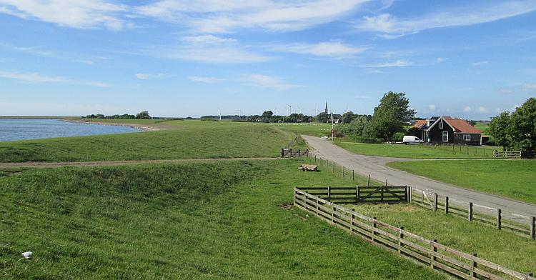 A typical dutch dyke with a large body of water to one side and flat lush green farmland on the other