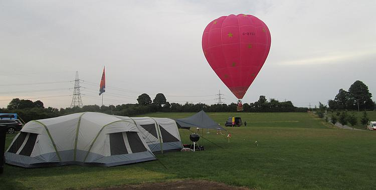 A large red hot air balloon leave the campsite at Far Peak