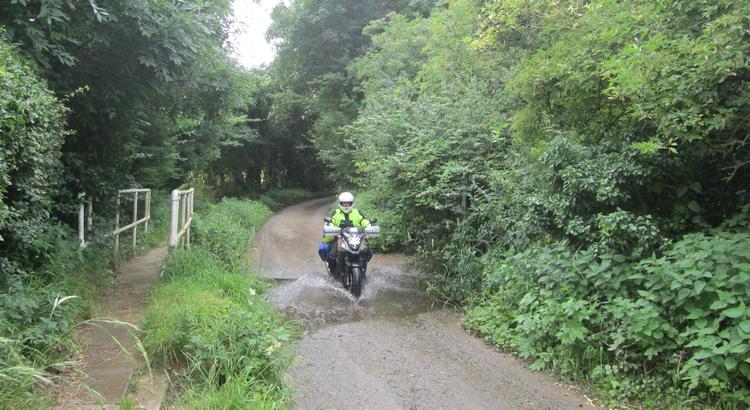 Ren splashes through a tiny little ford on his motorcycle in Folkingham