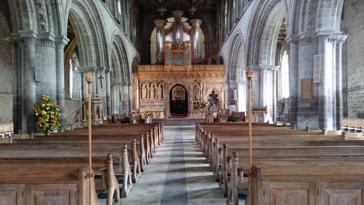 Columns and woodwork and a massive organ and pews inside St Davids Cathedral