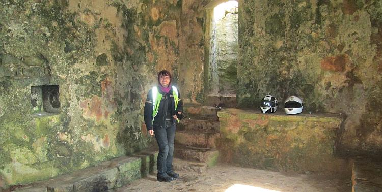 Sharon stands in the chapel, stone walls, stone seat and stone alter