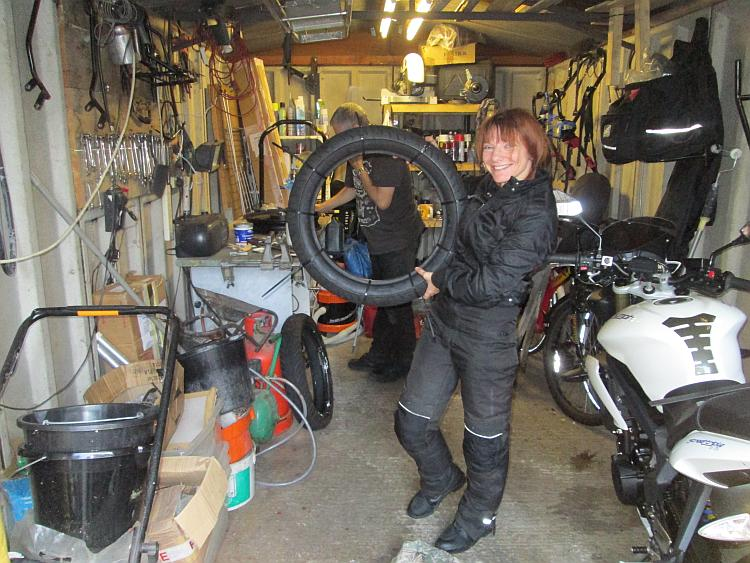 A garage filled with tools, shelves and equipment and Sharon holding a tyre