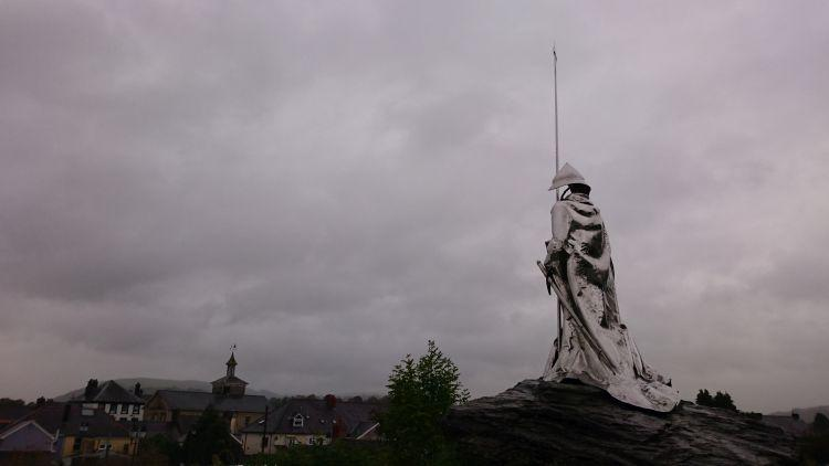 The steeley statue overlooks the town under heavy grey skies
