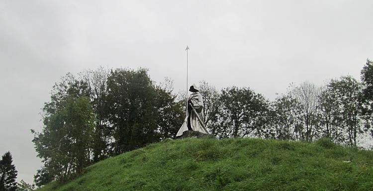 The shiny steel statue stands tall on a hill