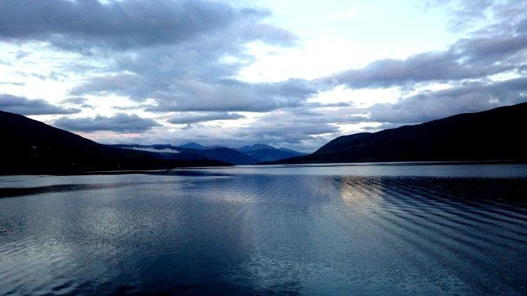The skies are huge and many shades of blue across a still Loch Broom at Ullapool