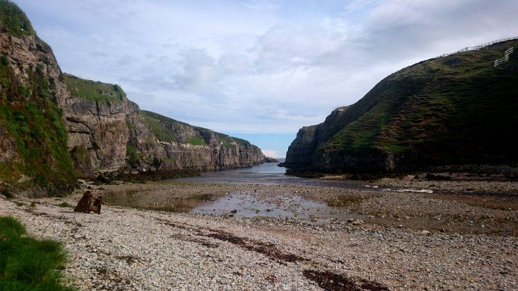 Looking out from Smoo Cave we see a steep sided cove with a river running out to the sea