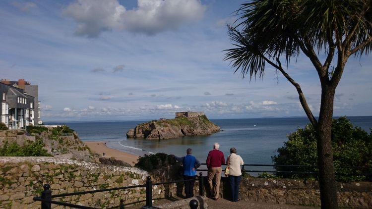 Between palm trees and holiday makers we see St Catherine's island out to sea from Tenby