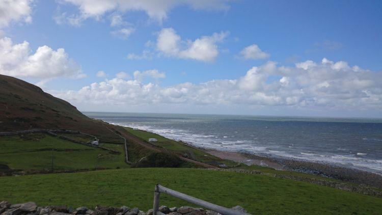 Hills roll down across fields to a narrow shoreline then the sea. Blue skies with light clouds