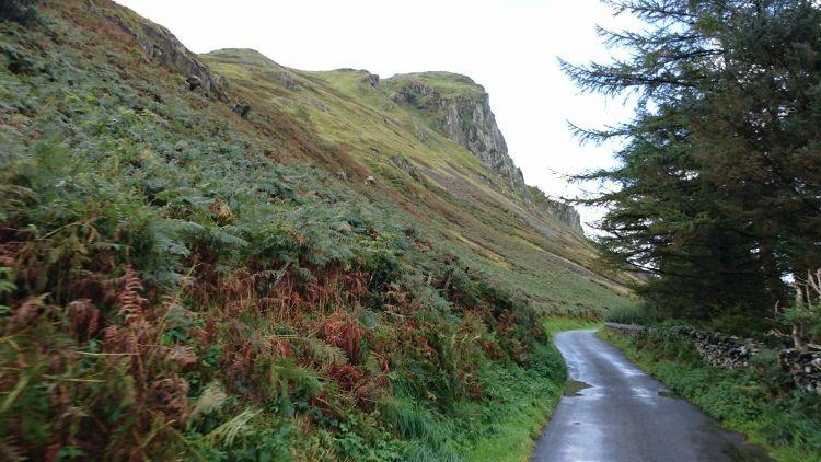 Steep fern covered hillsides, rocky outcrops and farmland in Wales