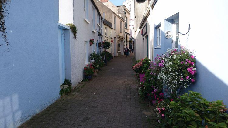 light blue and white painted houses line a narrow street highlighted with sun