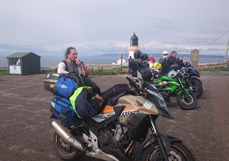 Ren stands by his Honda CB500X at Dunnet Head. Ren's bike is sandy beige coloured