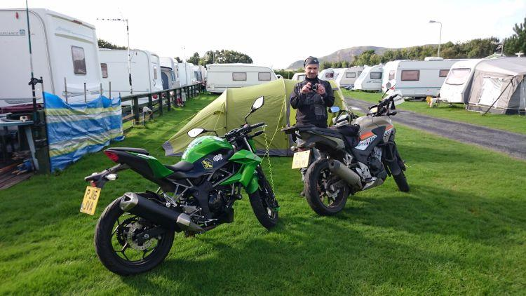 Ren is stood outside the tent taking pictures surrounded by caravans and the motorcycles