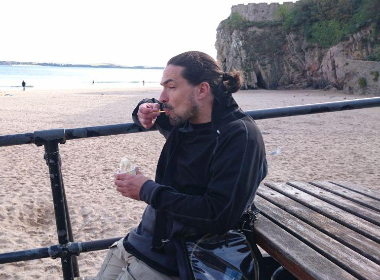 Ren is greedily shovelling ice cream into his face with the beach behind him at Tenby