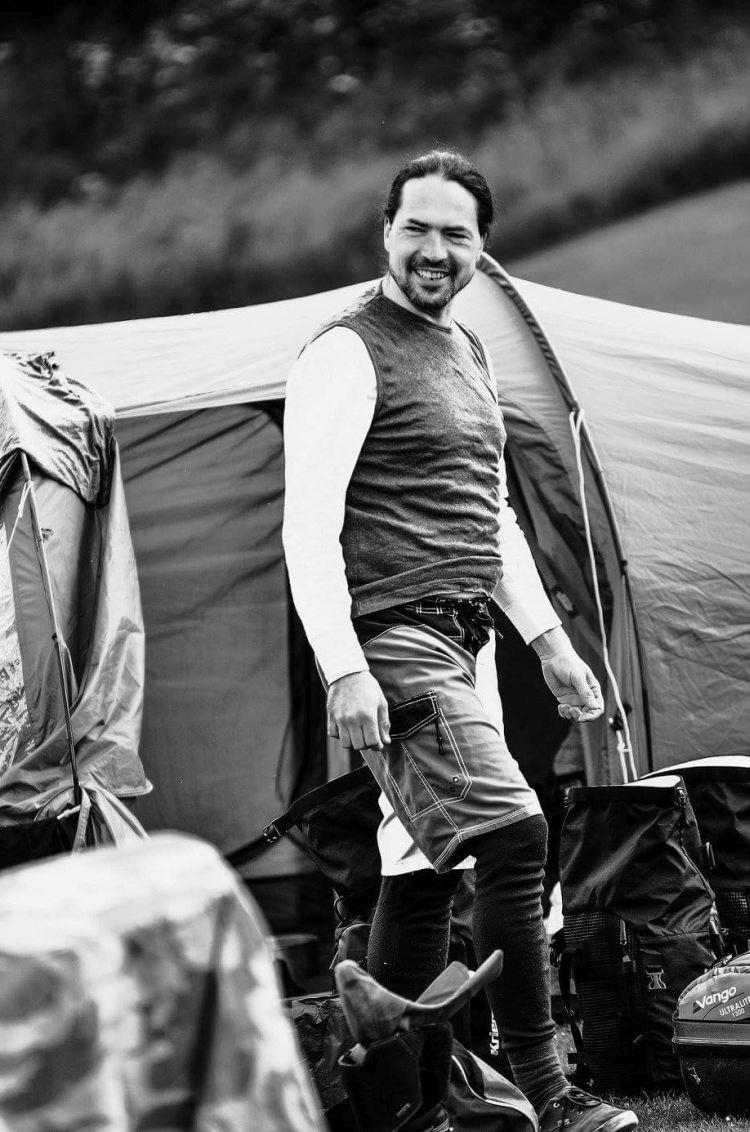 Ren is smiling emerging from the tent in an artistic black and white shot