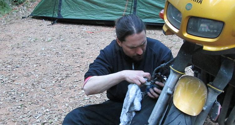 Ren looks intensely at the brake calliper he's working on at a campsite
