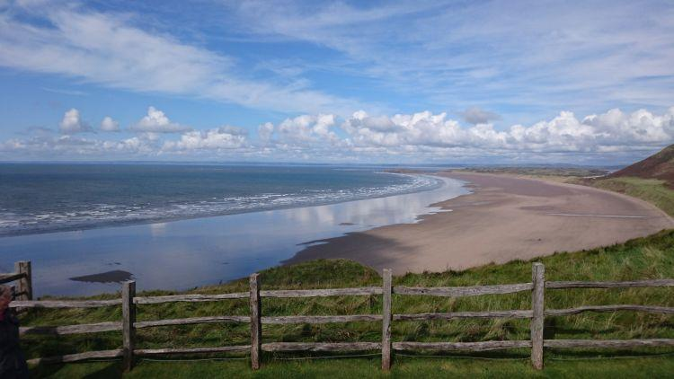 Seen from the bluff above, Rhossili beach stretches out into the distance with blue skies