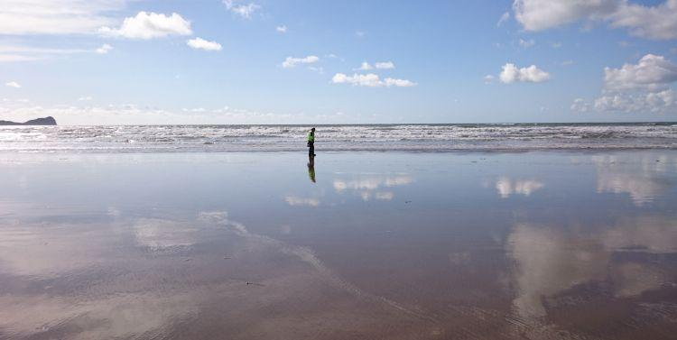 Ren stands alone at the shoreline with the sky reflected off the wet sands of the beach