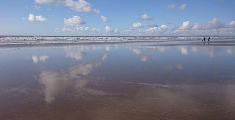 The sky is reflected on the wet sands at Rhossili Beach