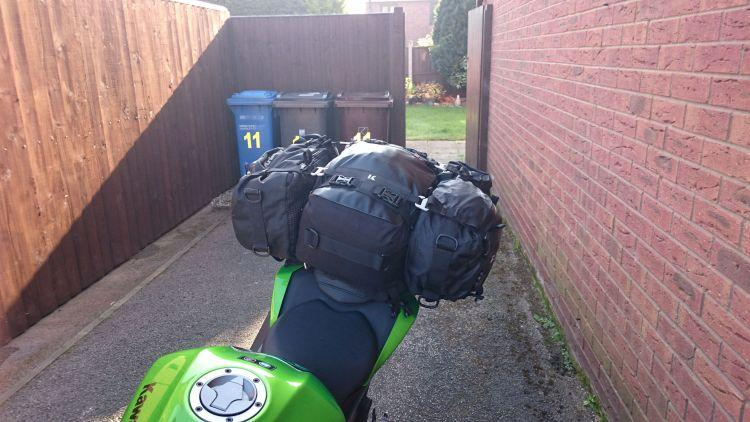 Three black bags tightly packed rest on the narrow rear seat of Sharon's Kawasaki