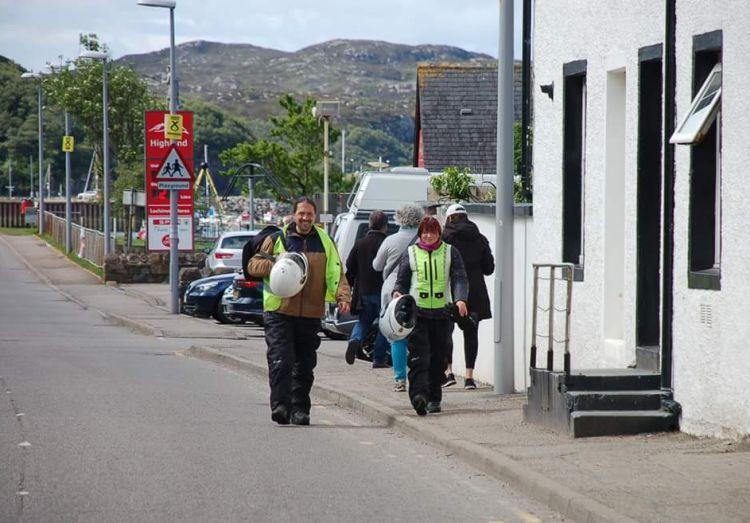 Sharon and Ren are walking through Lochinver in all their bike gear