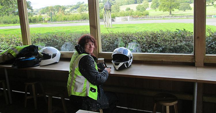 Sharon drinking tea and smiling at the camera surrounded by bike gear